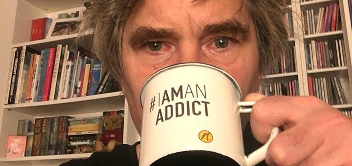 Jens trinkt aus Tasse mit Aufdruck #IAMANADDICT und nimble logo