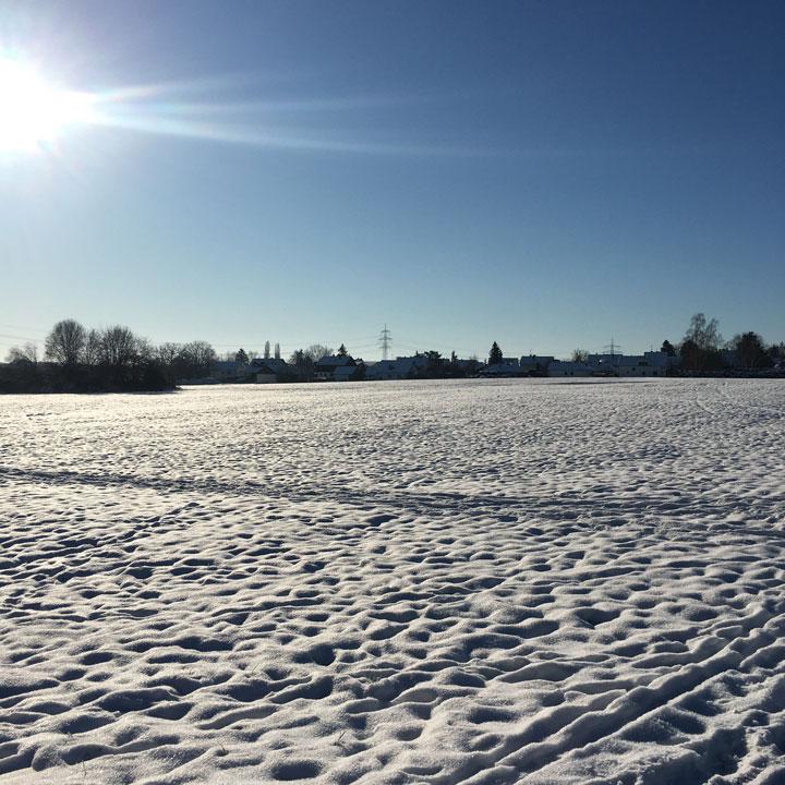 Verschneite Wiese und Dorfsilouette in strahlendem Sonnenschein